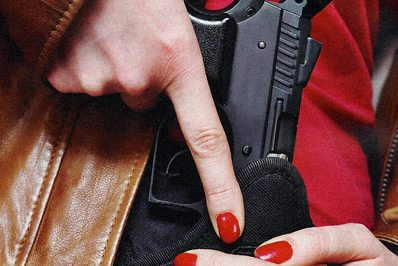 woman pulling handgun from holdster